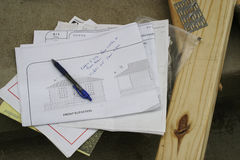 House Plans. Folded house blueprints with pen and lumber Stock Photography