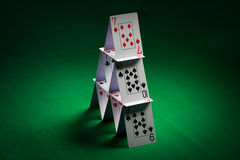 House of playing cards on green table cloth Stock Images