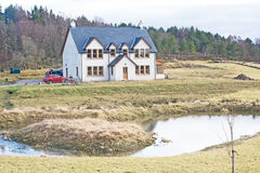House with a pond. An image of a modern house in the Scottish countryside surrounded by fields and forest with a pond for ducks Stock Photography