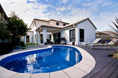 House With Pool. A white modern house with a cool blue pool in the foreground Royalty Free Stock Images