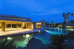 House With Pool In Backyard At Dusk. Illuminated house exterior with swimming pool in backyard at dusk Stock Photos