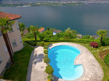 House with pool over lake. Mansion like house with round tower and palm tree an pool resides high over a lake Stock Photo
