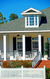 House with Porch and Fence. Elegant family home with inviting front porch and white picket fence Royalty Free Stock Photography