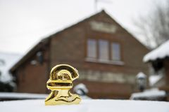House price freeze pound sign in snow. In front of a house stock photography