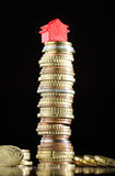 House prices. Model house on a stack of coins representing high prices on real estate market Stock Photos
