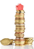 House prices. Model house on a stack of coins representing high prices on real estate market Stock Image