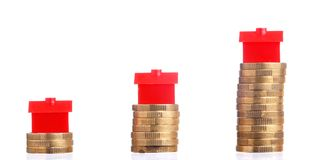 House prices. Red small houses on top of stacks of coins isolated on white background Royalty Free Stock Photography
