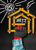 House Project - Wooden Meter on Blackboard. Hand holding a wooden meter ruler in the shape of house with sun, door, window and smoke from the chimney. On a stock illustration