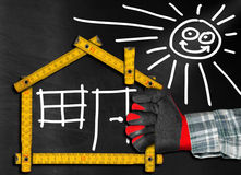 House Project - Wooden Meter on Blackboard. Hand holding a wooden meter ruler in the shape of house with sun, door, window and smoke from the chimney. On a royalty free illustration