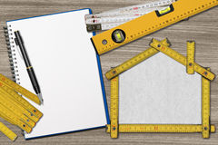 House Project - Yellow Wooden Meter. House project concept. Wooden meter ruler in the shape of house with pencil, empty notebook, two meter tools and spirit vector illustration