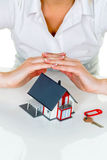 House is protected. Woman holding hands over a model house Stock Photo