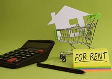 House put in a shopping cart and coin, calculator on the desk. Savings for home, buying houses, sell houses, real estate or housing benefit conceptn royalty free stock photos
