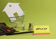 House put in a shopping cart and coin, pen, calculator on the desk. Savings for home, buying houses, sell houses, real estate or housing benefit concept royalty free stock image