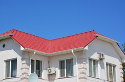 House metal roofing with roof gutter. House red metal roofing with roof gutter stock image
