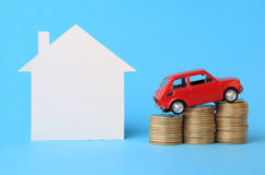 House, red miniature car and money. On blue Stock Image