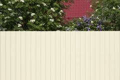 The house with a red roof and a garden is blocked by a tall whit. E fence Stock Photography