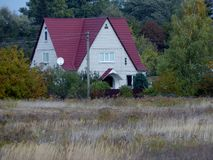 House with a red roof near the forest royalty free stock photos