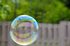 House reflected in a bubble on the left floating past a out of focus fence stock photos