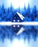 The house is reflected in smooth ice. From the sky the snow falls. Stock Photos