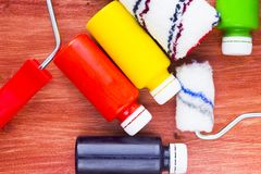 House renovation concept, paint cans and brushes. House renovation, bottles with paint and paint roller on the old wooden background top view stock photo