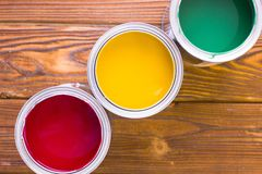 House renovation concept, colorfull paint cans on dark wooden background royalty free stock photography