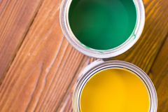 House renovation concept, colorfull paint cans on dark wooden background royalty free stock image