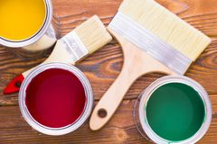 House renovation concept, colorfull paint cans and paintbrushes on dark wooden background royalty free stock photography