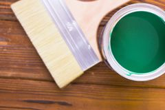 House renovation concept, colorfull paint cans and paintbrushes on dark wooden background royalty free stock photo