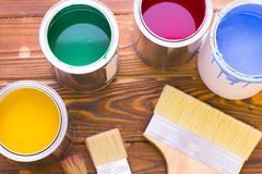 House renovation concept, colorfull paint cans and paintbrushes on dark wooden background stock images