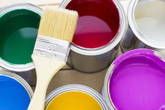House renovation concept, colorfull paint cans and paintbrushes on wooden background. Top view stock photo