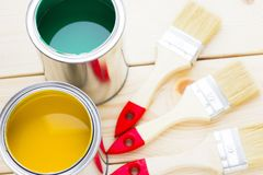 House renovation concept, colorfull paint cans and paintbrushes on wooden background. Top view stock image