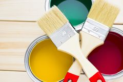 House renovation concept, colorfull paint cans and paintbrushes on wooden background. Top view royalty free stock photography