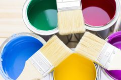 House renovation concept, colorfull paint cans and paintbrushes on wooden background. Top view royalty free stock images