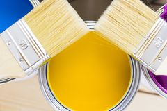 House renovation concept, colorfull paint cans and paintbrushes on wooden background. Top view royalty free stock photos