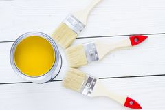 House renovation concept, colorfull paint cans and paintbrushes on wooden background stock photo
