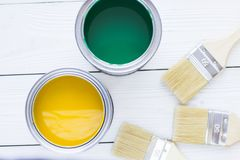 House renovation concept, colorfull paint cans and paintbrushes on wooden background. Top view stock photos