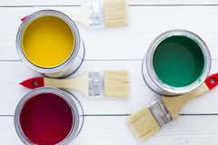 House renovation concept, colorfull paint cans and paintbrushes on wooden background. Top view royalty free stock photo