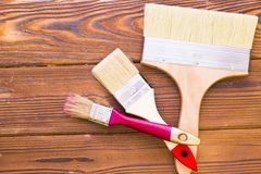 House renovation concept, colorfull paintbrushes on dark wooden background royalty free stock photography