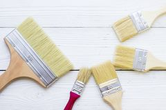 House renovation concept, colorfull paintbrushes on wooden background stock photo