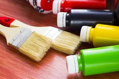 House renovation concept, paint cans and brushes. House renovation, bottles with paint and paintbrushes on the old wooden background stock images