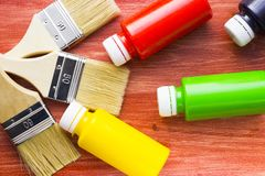 House renovation concept, paint cans and brushes. House renovation, bottles with paint and paintbrushes on the old wooden background royalty free stock photography