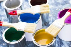 House renovation concept, paint cans and brushes. House renovation, paint cans and paintbrushes on blue mystic background royalty free stock photos