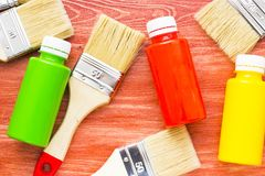 House renovation concept, paint cans and brushes. House renovation, paint cans and paintbrushes on the old wooden background top view stock images