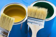 House renovation concept, paint cans and brushes. House renovation, paint cans and paintbrushes on blue background royalty free stock photo
