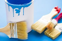 House renovation concept, paint cans and brushes. House renovation, paint cans and paintbrushes on blue background top view royalty free stock photo