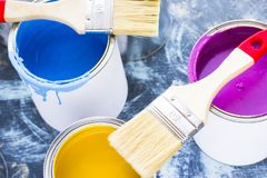 House renovation concept, paint cans and brushes. House renovation, paint cans and paintbrushes on blue mystic background stock photos