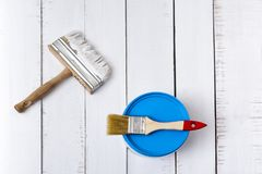 House renovation concept. Two paintbrushe and paint bucket on a background of white, shabby wooden planks. Directly above stock photo