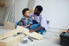 House renovation. Cute boy talking to father while drilling wooden plank during house renovation stock image