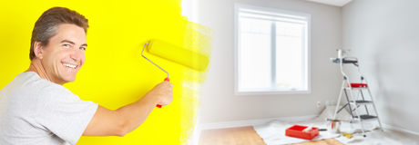 House renovation. Handsome man with painting roller. House renovation background royalty free stock image