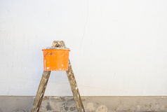 House renovation, ladder and bucket in front of an empty house wall. Royalty Free Stock Photo